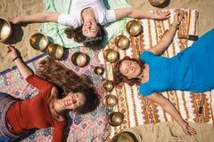 Τρία όμορφα θηλυκά που ξαπλώνουν ως mandala με τα τραγουδώντας κύπελλα σε μια όχθη ποταμού Στοκ Φωτογραφίες