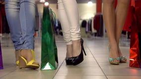 Τρία όμορφα κορίτσια με τις τσάντες αγορών πηγαίνουν στενό σε επάνω ποδιών εμπορικών κέντρων σε αργή κίνηση φιλμ μικρού μήκους