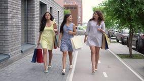 Τρία όμορφα κορίτσια περπατούν κάτω από την οδό με τις συσκευασίες στα χέρια τους μετά από να ψωνίσουν 4K απόθεμα βίντεο