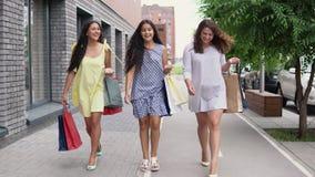 Τρία όμορφα κορίτσια περπατούν κάτω από την οδό με τις τσάντες στα χέρια τους μετά από να ψωνίσουν, έχοντας μια καλή διάθεση 4K απόθεμα βίντεο