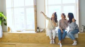 Τρία όμορφα κορίτσια πυροβολούν selfie καθμένος στο παράθυρο Φίλες που έχουν το γέλιο διασκέδασης στην κρεβατοκάμαρα απόθεμα βίντεο