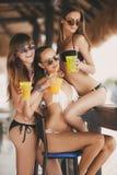 Τρία όμορφα κορίτσια σε έναν φραγμό στην παραλία στοκ φωτογραφία