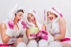 Τρία όμορφα κορίτσια στο κοστούμι κουνελιών αισθάνονται τη συγκινημένη εξέταση το λάχανο Στοκ Εικόνα