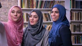 Τρία όμορφα μουσουλμανικά θηλυκά hijab παίρνουν τις εικόνες και selfie με το τηλέφωνο στεμένος εσωτερικός, βιβλία στο υπόβαθρο φιλμ μικρού μήκους