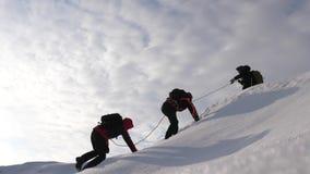 τρία Alpenists το χειμώνα αναρριχούνται στο σχοινί στο βουνό Οι ταξιδιώτες αναρριχούνται στο σχοινί στη νίκη τους μέσω του ανήφορ στοκ εικόνες