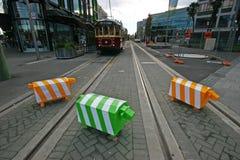Τρία blocky ζωικά γλυπτά Ζωηρόχρωμοι στυλίσκοι ασφάλειας κυκλοφορίας προβάτων στο δρόμο με τις διαδρομές τροχιοδρομικών γραμμών σ στοκ εικόνες με δικαίωμα ελεύθερης χρήσης