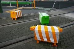 Τρία blocky ζωικά γλυπτά Ζωηρόχρωμοι στυλίσκοι ασφάλειας κυκλοφορίας προβάτων στο δρόμο με τις διαδρομές τροχιοδρομικών γραμμών σ στοκ εικόνα με δικαίωμα ελεύθερης χρήσης