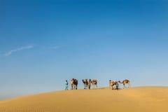 Τρία cameleers (οδηγοί καμηλών) με τις καμήλες στους αμμόλοφους Thar des Στοκ Εικόνα