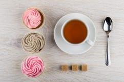 Τρία cupcakes με την κρέμα, κουταλάκι του γλυκού, φλυτζάνι του τσαγιού, άμορφη ζάχαρη Στοκ φωτογραφία με δικαίωμα ελεύθερης χρήσης