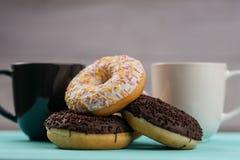 Τρία donuts, ένα πάνω από άλλη, σοκολάτα και άσπρη κρέμα Πίσω από τους είναι δύο κούπες με ένα ζεστό ποτό Στοκ Εικόνες