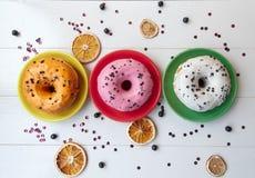 Τρία donuts που βρίσκονται στα ζωηρόχρωμα πιάτα στο άσπρο ξύλινο υπόβαθρο Στοκ εικόνα με δικαίωμα ελεύθερης χρήσης