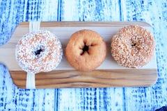 Τρία donuts στον ξύλινο τέμνοντα πίνακα Στοκ Εικόνες