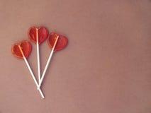 Τρία lollipops στο καφετί υπόβαθρο Στοκ Φωτογραφίες