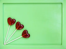 Τρία lollipops στο πράσινο υπόβαθρο στοκ εικόνες