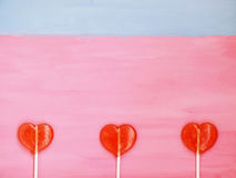 Τρία lollipops στο ρόδινο και μπλε υπόβαθρο Στοκ Εικόνες