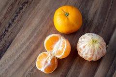 Τρία satsuma πορτοκάλια σε έναν αγροτικό ξύλινο πίνακα στοκ φωτογραφία