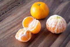 Τρία satsuma πορτοκάλια σε έναν αγροτικό ξύλινο πίνακα στοκ φωτογραφίες