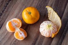 Τρία satsuma πορτοκάλια σε έναν αγροτικό ξύλινο πίνακα στοκ εικόνες με δικαίωμα ελεύθερης χρήσης