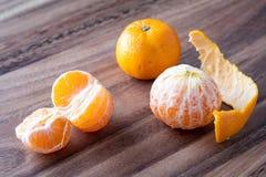 Τρία satsuma πορτοκάλια σε έναν αγροτικό ξύλινο πίνακα στοκ εικόνα με δικαίωμα ελεύθερης χρήσης