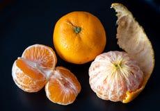Τρία satsuma πορτοκάλια σε ένα μαύρο πιάτο στοκ εικόνες