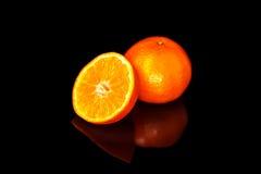 Τρία tangerines σε έναν μαύρο καθρέφτη Στοκ Εικόνα