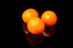 Τρία tangerines σε έναν μαύρο καθρέφτη Στοκ Φωτογραφίες