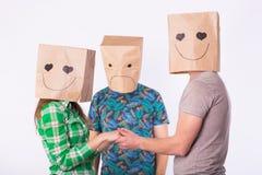Τρίγωνο αγάπης, ζηλοτυπία και απλήρωτη έννοια αγάπης - γυναίκα και άνδρας με τις τσάντες πέρα από τα κεφάλια που κρατούν τα χέρια στοκ φωτογραφίες με δικαίωμα ελεύθερης χρήσης