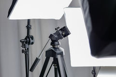 Τρίποδο καμερών σε ένα στούντιο φωτογραφιών με τον εξοπλισμό αστραπής Στοκ φωτογραφία με δικαίωμα ελεύθερης χρήσης