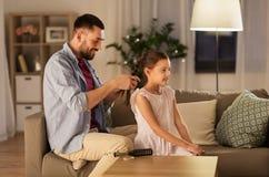 Τρίχα κορών πλεξίματος πατέρων στο σπίτι στοκ φωτογραφία