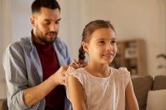 Τρίχα κορών πλεξίματος πατέρων στο σπίτι στοκ φωτογραφία με δικαίωμα ελεύθερης χρήσης