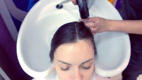 Τρίχα του πελάτη πλύσης κουρέων στο σαλόνι ομορφιάς στο νεροχύτη απόθεμα βίντεο
