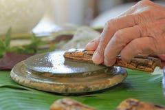 Τρίψιμο φλοιών χορταριών Thanaka στην πλάκα πετρών kyauk pyin στοκ εικόνα