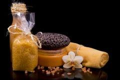 Τρίψτε και κρέμα σωμάτων, πορτοκαλιά πετσέτα υφασμάτων, λουλούδι ορχιδεών και θάλασσα Στοκ Φωτογραφία