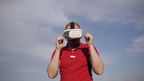 Τραίνα ατόμων που εγκιβωτίζουν στα γυαλιά VR στο πάρκο στο υπόβαθρο μπλε ουρανού απόθεμα βίντεο