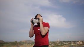 Τραίνα ατόμων που εγκιβωτίζουν στα γυαλιά VR στο πάρκο στο υπόβαθρο μπλε ουρανού φιλμ μικρού μήκους