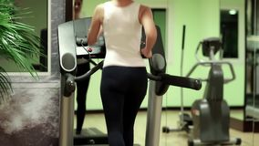 Τραίνα γυναικών στη γυμναστική Γυναίκα που περπατά treadmill στη γυμναστική απόθεμα βίντεο
