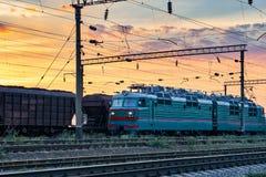Τραίνα και βαγόνια εμπορευμάτων, υποδομή σιδηροδρόμου, όμορφο ηλιοβασίλεμα και ζωηρόχρωμος ουρανός, μεταφορά και βιομηχανική έννο Στοκ Φωτογραφία