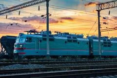 Τραίνα και βαγόνια εμπορευμάτων, υποδομή σιδηροδρόμου, όμορφο ηλιοβασίλεμα και ζωηρόχρωμος ουρανός, μεταφορά και βιομηχανική έννο Στοκ Εικόνες