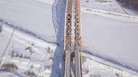 Τραίνο άποψης κηφήνων που κινείται στη γέφυρα σιδηροδρόμων πέρα από το χειμερινό ποταμό Κυκλοφορία τραίνων στη γέφυρα αναστολής μ φιλμ μικρού μήκους