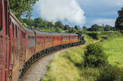 Τραίνο ατμού που τραβά τα επιβατικά αυτοκίνητα Στοκ Φωτογραφία