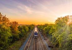 Τραίνο μέσω της φύσης κατά τη διάρκεια ενός θερμού ηλιοβασιλέματος Στοκ εικόνες με δικαίωμα ελεύθερης χρήσης