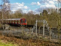 Τραίνο Μετρό του Λονδίνου που περνά από στη διαδρομή σε Chorleywood στοκ φωτογραφία με δικαίωμα ελεύθερης χρήσης