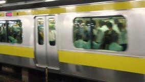 Τραίνο που φθάνει σε μια πλατφόρμα σταθμών μετρό ενώ οι κάτοχοι διαρκούς εισιτήριου περιμένουν στη γραμμή, Τόκιο, Ιαπωνία απόθεμα βίντεο