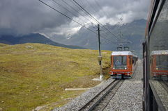 Τραίνο στην κίνηση και τα ελβετικά βουνά Άλπεων στο υπόβαθρο Στοκ Εικόνες
