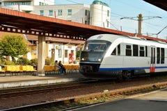 Τραίνο στο σταθμό με τους ανθρώπους που περιμένουν στα περιμένοντας καθίσματα Στοκ Εικόνες