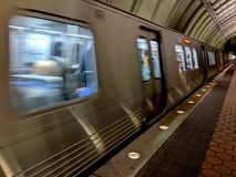 Τραίνο ΣΥΝΕΧΩΝ μετρό που τραβά στο σταθμό στοκ εικόνα