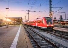 Τραίνο υψηλής ταχύτητας επιβατών στο σιδηροδρομικό σταθμό στο ηλιοβασίλεμα στοκ φωτογραφία με δικαίωμα ελεύθερης χρήσης