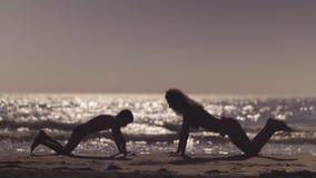Τραίνο Mom και γιων στην παραλία Η ώθηση επάνω στην άσκηση κοντά στη θάλασσα απόθεμα βίντεο