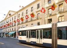 Τραίνο rue Corraterie Street με τις ελβετικές σημαίες στη Γενεύη Ελβετός Στοκ Φωτογραφίες