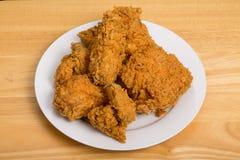 Τραγανό τηγανισμένο κοτόπουλο στο άσπρο πιάτο και τον ξύλινο πίνακα Στοκ Εικόνες